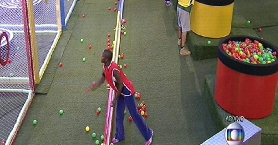 """29.jan.2015 - Integrante do time vermelho, Angélica tenta jogar bolinhas para Amanda e Tamires dentro da gaiola durante a segunda prova do lídero do """"BBB15"""""""