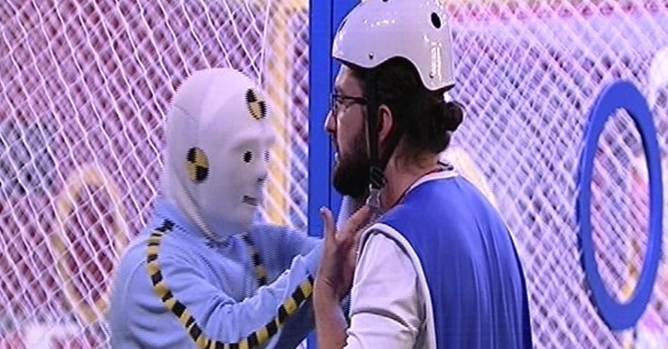 """29.jan.2015 - Integrante mascarado da produção do """"BBB15"""" ajuda Marco a colocar capacete para disputar a segunda prova do líder"""