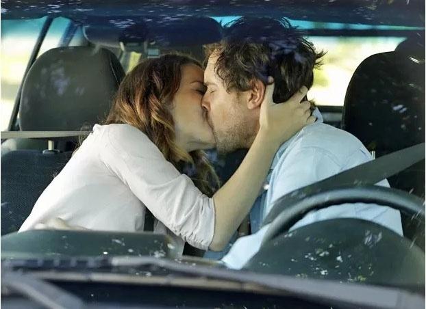 Laura (Nathalia Dill) e Caíque (Sergio Guizé) se beijam em
