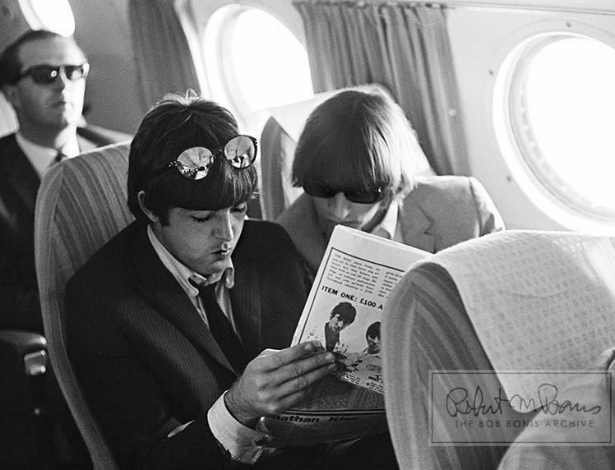 Coleção de fotos raras dos Beatles e dos Rolling Stones durante turnês nos EUA, na década de 1960, está à venda no eBay. Na imagem, Paul McCartney e Rigo Starr leem um artigo durante voo, em 1965. Na contracapa da revista, podemos ver uma foto da banda The Who