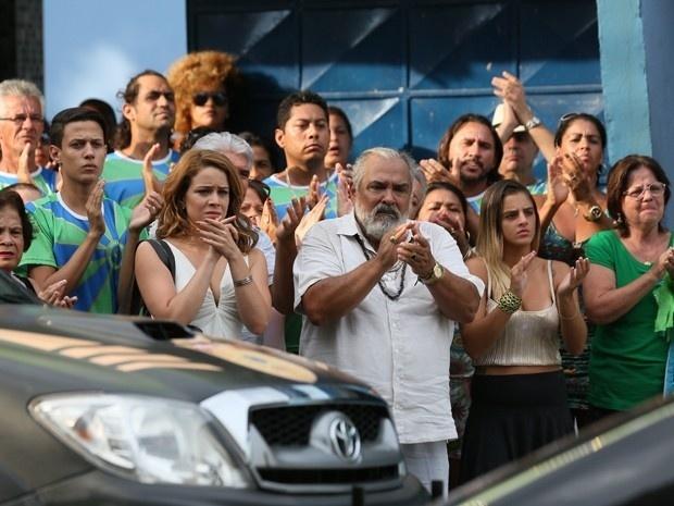Cristina, Antoninho e populares aplaudem o Comendador ao sair algemado do barracão