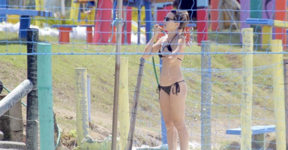 3.fev.2015 - Depois de caminhar, atriz Bianca Bin toma banho de mangueira na praia da Barra da Tijuca, no Rio de Janeiro