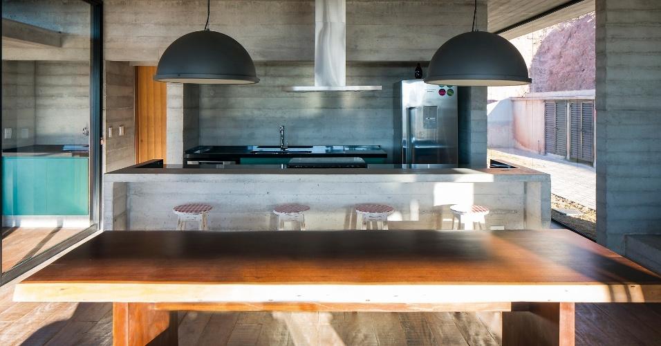Vedações envidraçadas são suportadas por caixilhos metálicos (alumínio) pintados de preto, para que não fiquem tão evidentes à noite. A mesa de jantar é acompanhada por bancos e está posta entre a cozinha americana (ao fundo) e a sala de estar. O piso até a bancada é de madeira de demolição (em segundo plano) e, na área de trabalho da cozinha, as superfícies são de cimento queimado. O projeto de arquitetura é assinado por André Becker