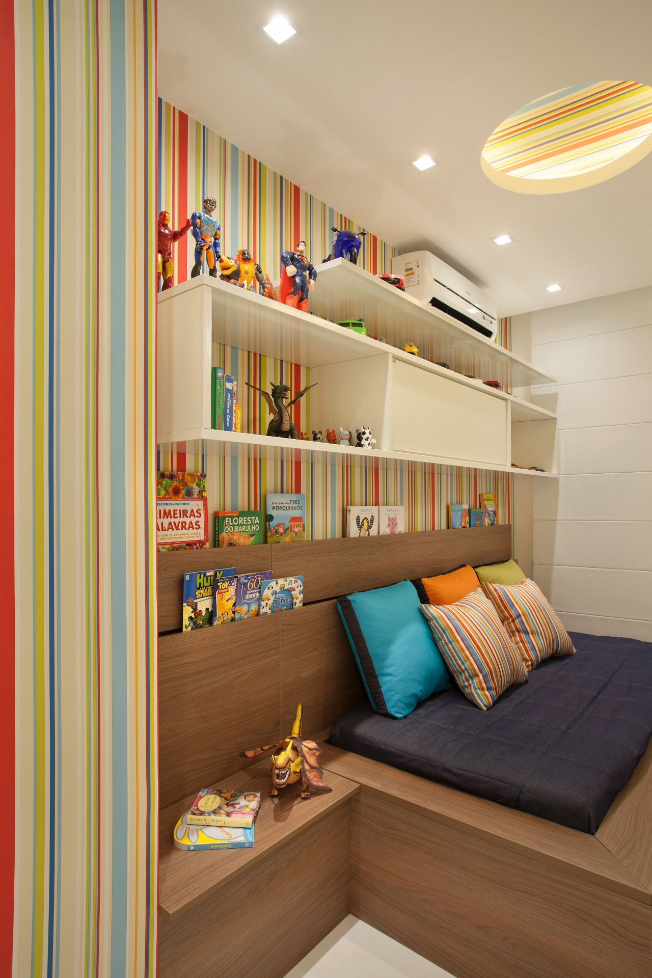 No quarto de menino, projetado por Claudia Pimenta e Patricia Franco, a cabeceira em madeira, integrada à cama, tem duas aberturas que auxiliam na organização dos livros e revistas. A cama foi desenhada pela dupla e executada em marcenaria, com encaixe para embutir o colchão
