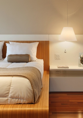 Para o projeto de um quarto pequeno, os arquitetos Eliane Fiuza, Gustavo Prado e Bel Vasconcelos optaram em fazer a cama e a cabeceira executadas em folhas de madeira de aspecto leve e veios bem marcados