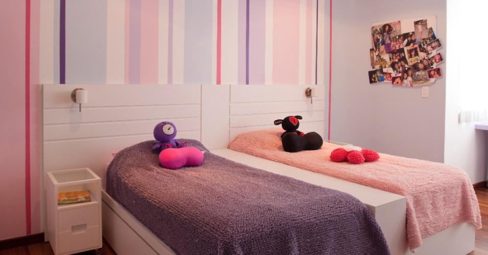 Para o quarto de duas meninas, a arquiteta Karina Korn desenhou uma cabeceira em laca branca e que integra as camas. Por outro lado, uma espécie de aparador entre os leitos divide o espaço