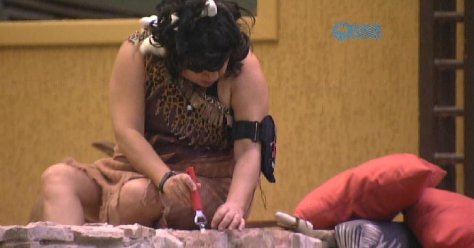 7.fev.2015 - Com a ajuda de um abridor, Mariza recupera pulseira presa em móvel de pedras