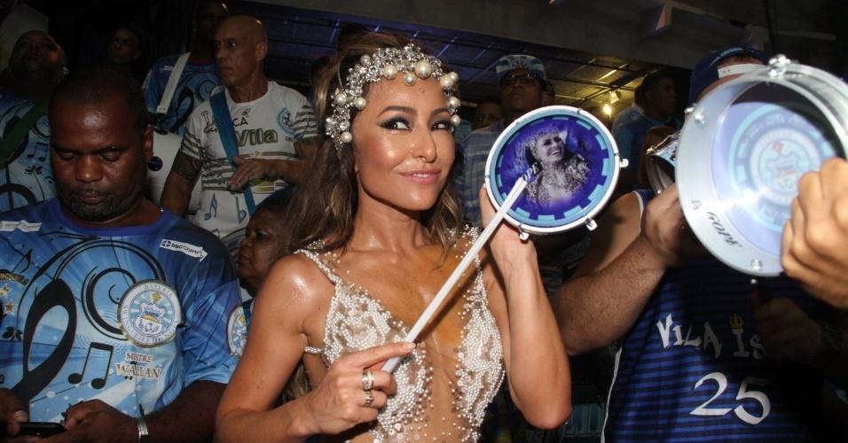 8.fev.2015 - De maiô transparente, Sabrina Sato toca tamborim com sua foto durante ensaio na quadra da Vila Isabel, no Rio de Janeiro