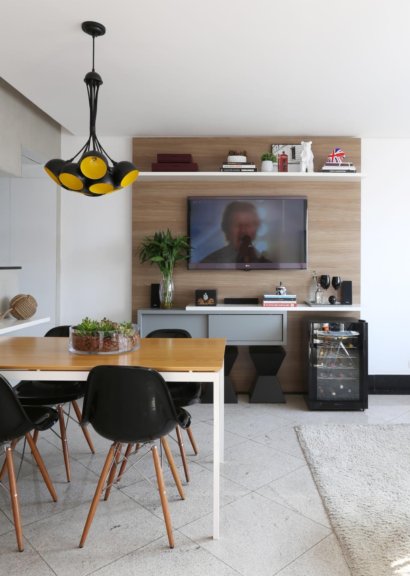 Como os moradores do apartamento no bairro Vila Olímpia, em São Paulo (SP), costumam receber amigos em casa, a arquiteta Duda Senna escolheu uma mesa de jantar (Oppa) que fica, em parte, encaixada sob o aparador (à esq.). O recurso economiza espaço no dia a dia, mas, caso haja mais do que quatro pessoas para uma refeição, o móvel pode ser deslocado para o centro e ganhar, ao redor de si, banquetas (que ficam dispostas junto ao painel do home theater, ao fundo)