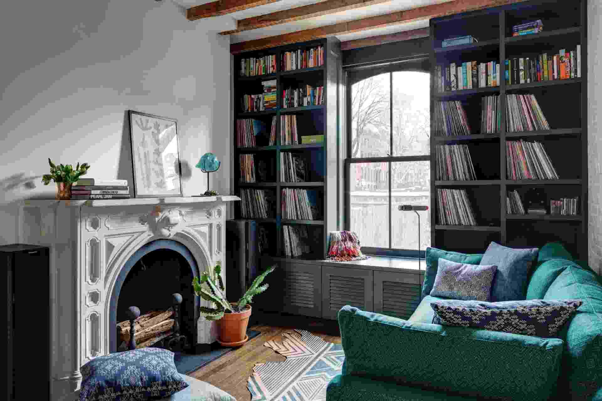A sala de estar conta com estantes que acomodam a coleção de vinis de David. O mobiliário tem pontos de cor e a lareira antiga é o destaque do ambiente (Imagem do NYT, usar apenas no respectivo material) - Bruce Buck/ The New York Times