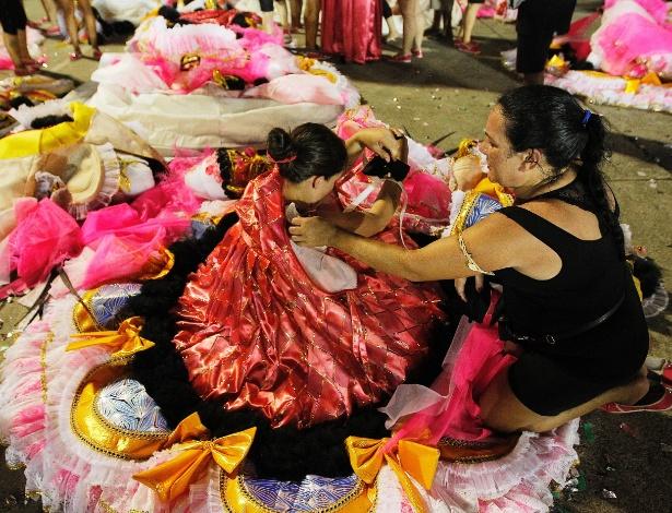 14.fev.2015 - Integrantes ajudam uns aos outros a tirarem suas fantasias depois do desfile da Acadêmicos do Tucuruvi