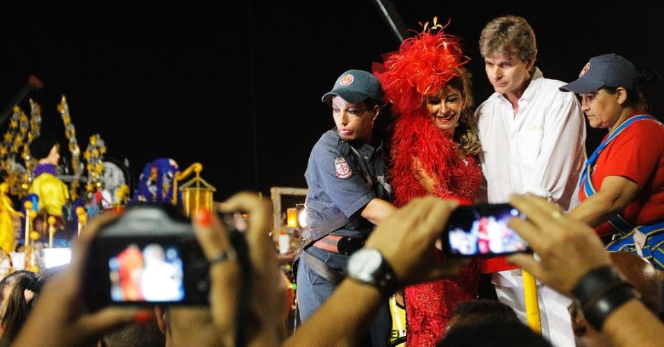 15.fev.2015 - Bombeiros ajudam Marília Pêra a descer do carro alegórico, após desfile da Mocidade Alegre