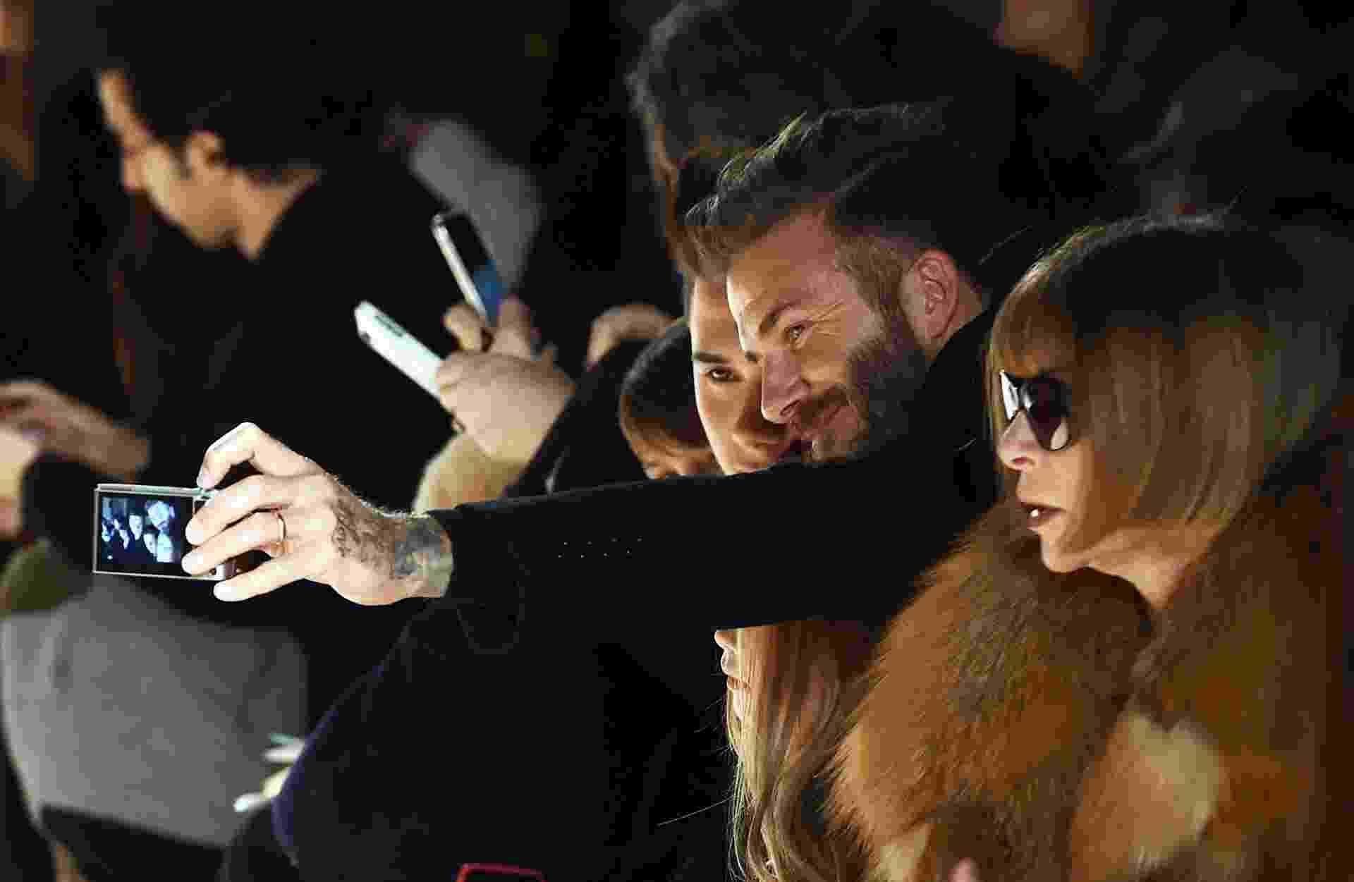 """15.fev.2015 - David Beckham faz um """"selfie"""" com o filho na primeira fila do desfile da coleção de Victoria Beckham na Semana de Moda de Nova York - AFP Photo/Jewel Samad"""