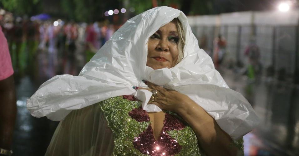 15.fev.2015 - A cantora Alcione se protege da chuva antes de entrar na Marquês de Sapucaí para o desfile da Mangueira