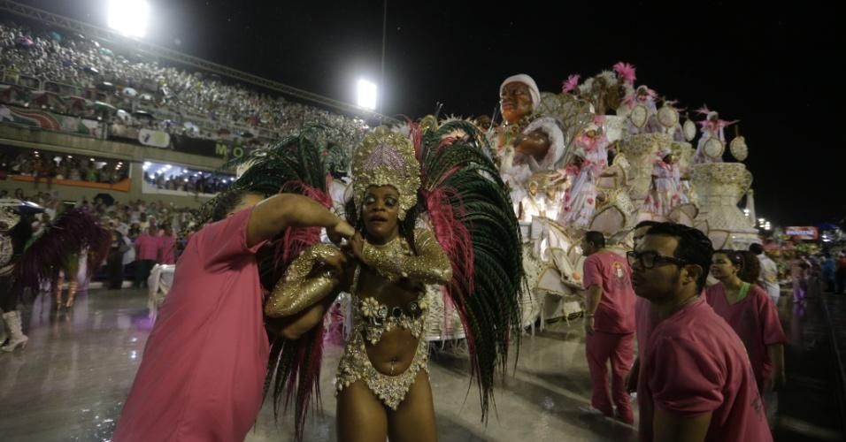 16.fev.2015 - Destaque da Mangueira recebe ajuda para arrumar a fantasia debaixo de chuva durante desfile na Sapucaí