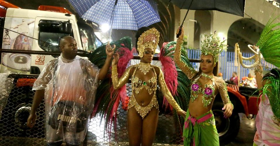16.fev.2015 - Passistas da Mangueira se protegem da chuva na Sapucaí