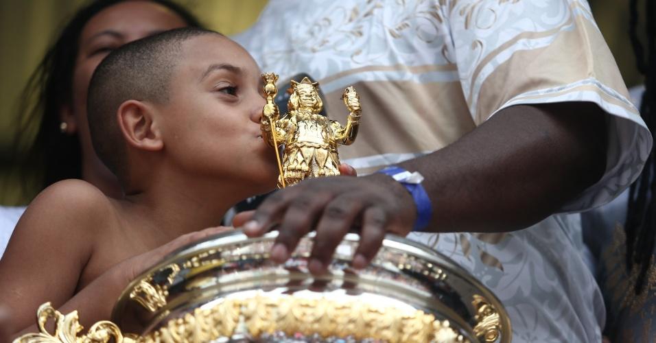17.fev.2015 - Jovem da comunidade beija o troféu do título do Carnaval de São Paulo conquistado pela escola de samba Vai Vai
