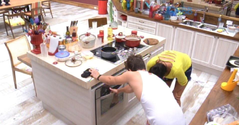 """17.fev.2015 - Talita prepara pudim na cozinha do """"BBB15"""". Rafael acorda a ajuda a aeromoça a acender o forno"""