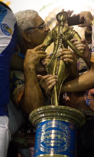 18.fev.2015 - Na taça da Beija-Flor, todas as mãos procuram a taça de campeã do Carnaval