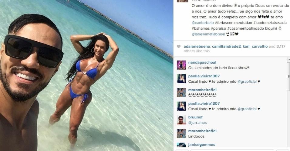 """21.fev.2015- Belo faz selfie nas Bahamas com Gracyanne Barbosa de biquíni ao fundo: """"O amor é o dom divino. É o próprio Deus se revelando a nós. O amor tudo refaz... Se algo nos falta o amor nos traz. Tudo é completo com amor. Te amo, @cantorbelo #feriascommeutudao #luademelatrasada #bahamas #paraiso #casamentoblindado"""", escreveu a morena na legenda da imagem no Instagram"""