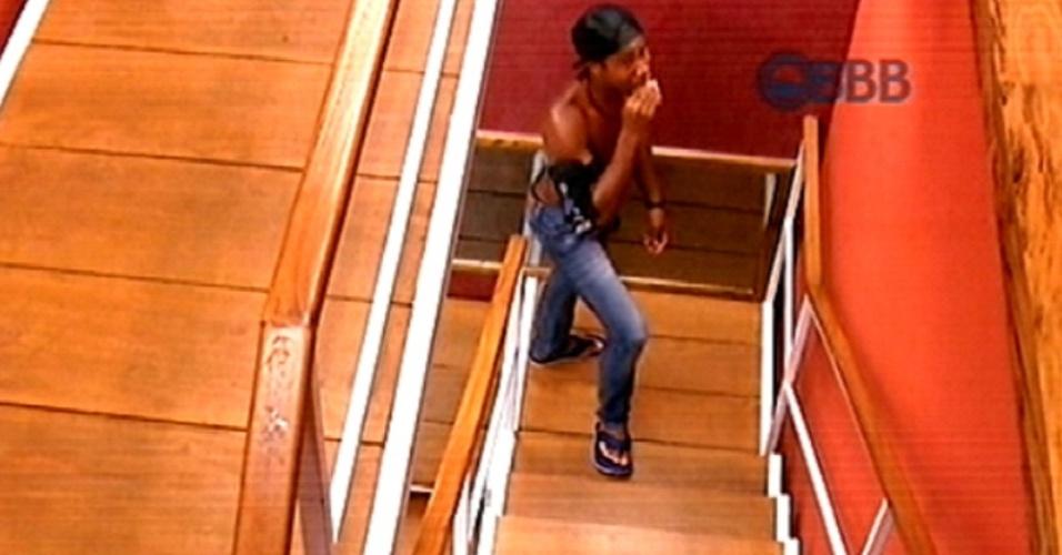 """23.fev.2015 - Integrante do grupo Tá Com Nada, Luan come nugget escondido na escada da academia do """"BBB15"""""""