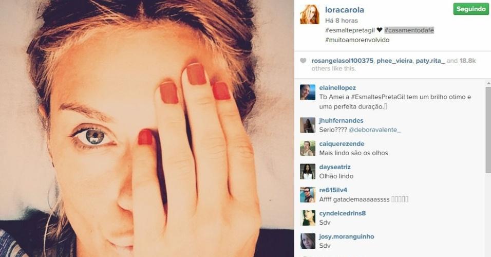24.fev.2015 - Carolina Dieckmann mostrou a cor que escolheu para exibir nas unhas durante o casório e aproveitou para fazer propaganda da linha de esmaltes da amiga Preta Gil.