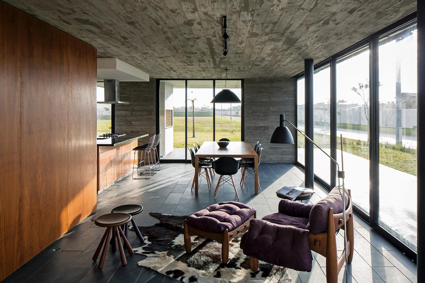 A transparência é a característica marcante da Casa Xan, projetada pelo escritório MAPA Architects, pois permite a integração entre interior e exterior através do fechamento em vidro, no pavimento térreo. O living reúne estar, jantar e cozinha e, ao fundo, é possível avistar a varanda com churrasqueira