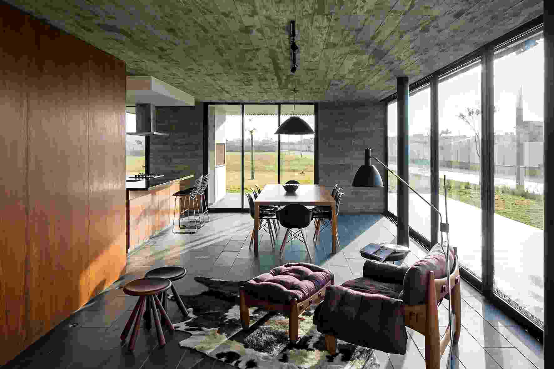 A transparência é a característica marcante da Casa Xan, projetada pelo escritório MAPA Architects, pois permite a integração entre interior e exterior através do fechamento em vidro, no pavimento térreo. O living reúne estar, jantar e cozinha e, ao fundo, é possível avistar a varanda com churrasqueira - Leonardo Finotti/ UOL