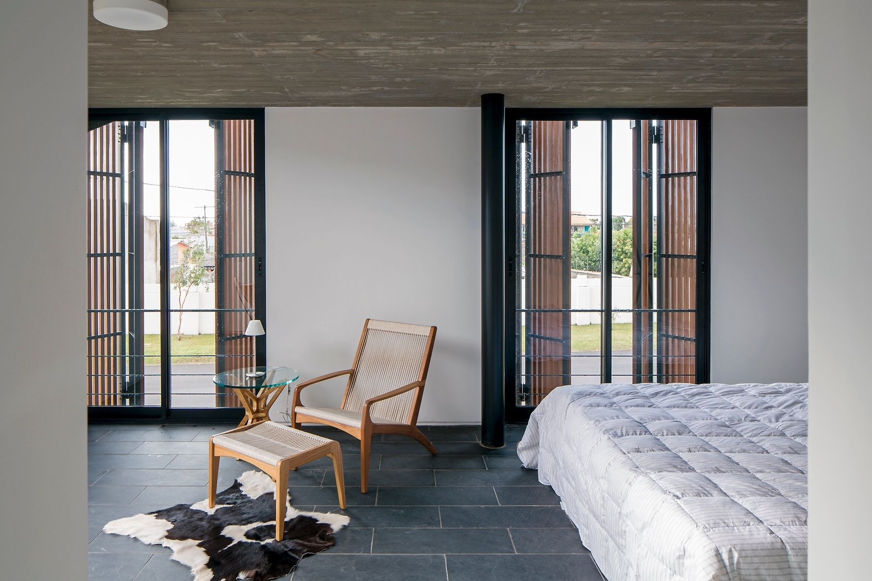 As portas-venezianas possuem brises de madeira itaúba, que controlam a insolação na suíte do casal. O quarto conta com espaço generoso que acomoda um pequeno estar. A Casa Xan foi projetada pelo escritório MAPA, no Rio Grande do Sul