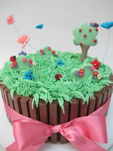 bolo sem pasta americana | O bolo trufado da Santo Açúcar ganhou barras de chocolate no acabamento para imitar um cercadinho. No topo, o jardim foi feito com glacê