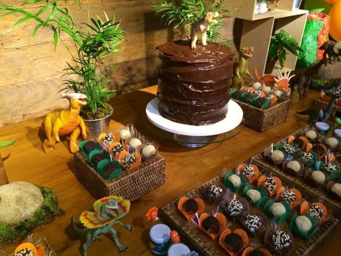 bolo sem pasta americana | Os dinossauros ganharam um bolo de chocolate, da Saimon Garcia, alto para representar uma montanha na mesa principal dessa festa de aniversário