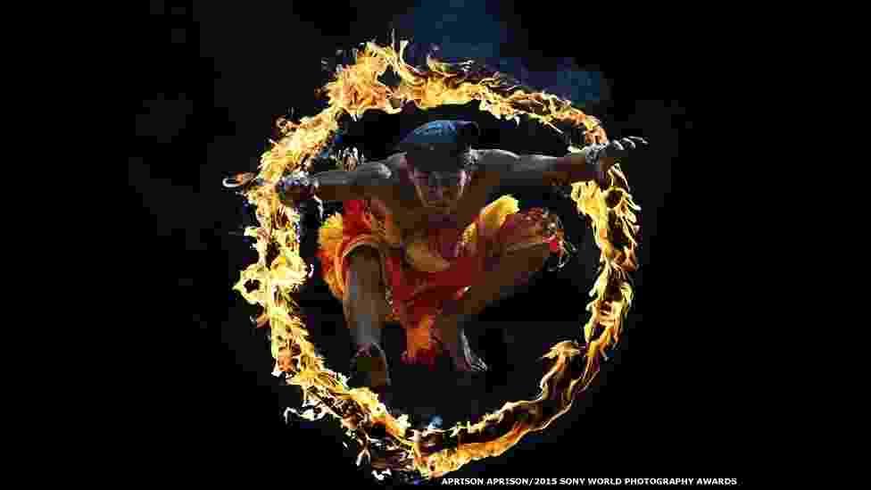 Esta imagem de Bujang Ganong saltando através de um círculo de fogo foi feita por Aprison-Aprison. Clicada na Indonésia, a foto foi selecionada para a categoria aberta Artes e Cultura - Sony World Photography Awards