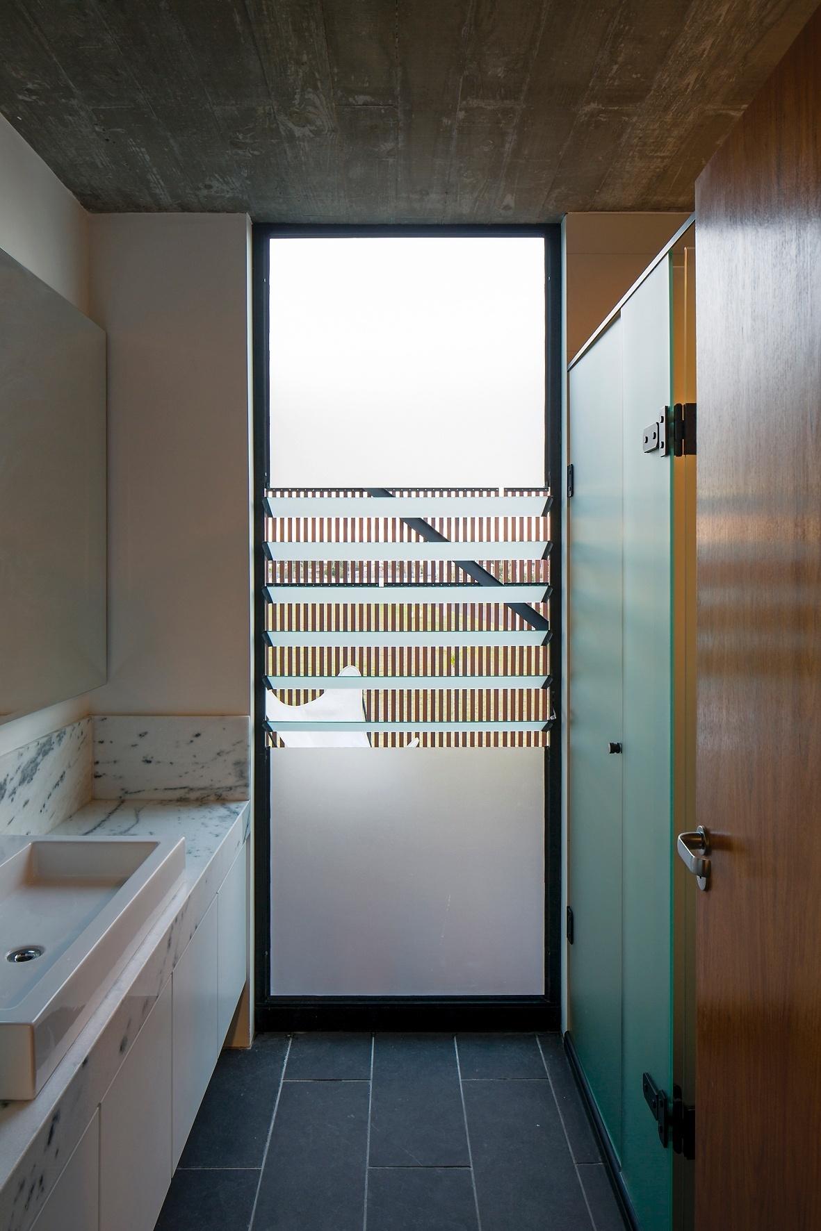 O banheiro do casal está interligado ao terraço através da janela do tipo basculante, acoplada a uma porta. Os vidros permitem a entrada de luz e ventilação natural. A Casa Xan foi projetada pelo escritório MAPA, no Rio Grande do Sul