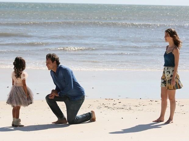 Caíque e Laura passeiam na praia quando Bella aparece para contar a novidade
