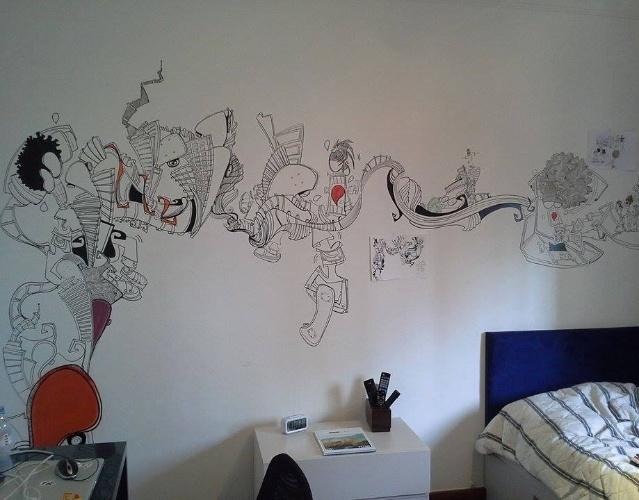 álbum com grafites para o quarto adolescente   Idealizado pela designer de interiores Paula Gambier (www.facebook.com/PaulaGambierInteriores) para um adolescente carioca, fã do estilo de vida em sua cidade, o quarto recebeu o grafite assinado por Marcelo Zuffo (www.vioti.com.br/clientes/marcelo-zuffo). O artista recorreu a caneta PX (tipo de caneta) e estêncil (desenho que pode ser delineado por corte ou perfuração em alguma superfície, como papel ou papelão) para traçar o desenho