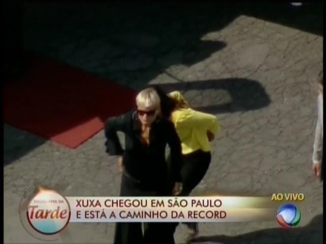 6.mar.2015- Xuxa desembarca em Congonhas de óculos escuros, calça e blusa preta. A chegada dela foi registrada ao vivo pela Record