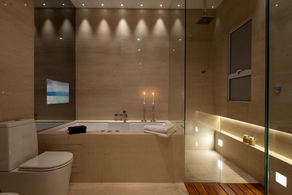 Com dez metros quadrados, este banheiro com design do arquiteto Ricardo Rossi serve à suíte de um casal. Um dos pontos altos do projeto é a iluminação da Wall Lamps, que propicia o clima acolhedor e permite aos proprietários assistirem à TV que está embutida atrás do espelho 'smart', da L'Vitrier, enquando curtem a hidromassagem da Pretty Jet. Separado pela divisória (à dir.) de vidro está o boxe com chuveiro de teto. Para arrematar a proposta, revestimento em Limestone Mont Dorê, da Mont Blanc