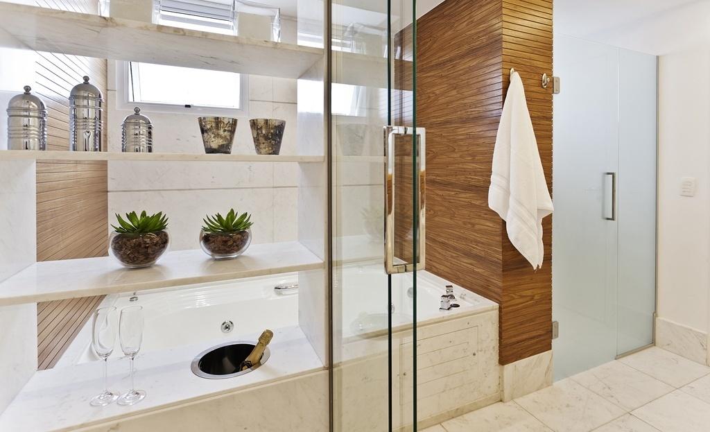 Com 12 m², este banheiro foi planejado pelo escritório Sesso & Dalanezi para um casal apreciador de bons vinhos, por isso um dos destaques do ambiente é a champanheira (à esq.) instalada próxima a banheira de hidromassagem, na base de mármore branco piguês. Para dar aumentar o aconchego, as paredes foram revestidas por madeira (freijó). Uma estante, também de mármore, abriga os itens de higiene