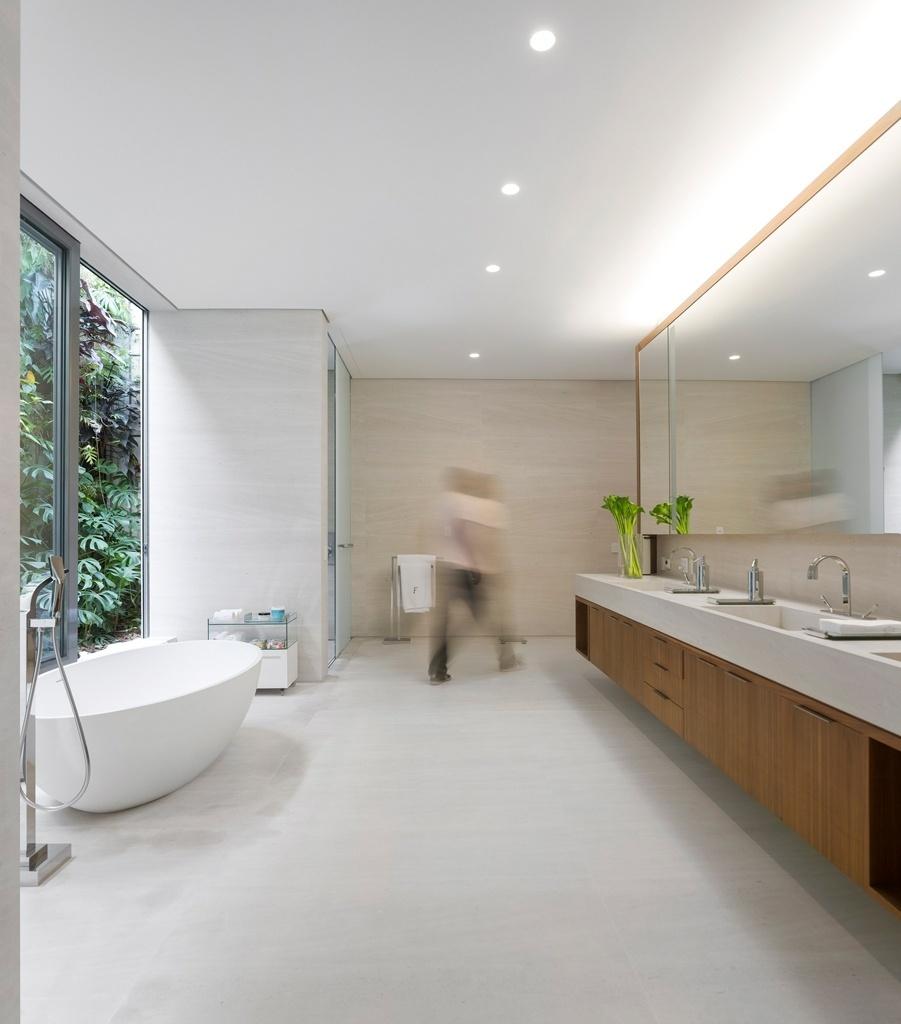 Com design limpo, o banheiro com 40 m² foi assinado pela arquiteta Fernanda Marques e é integrado ao verde graças ao jardim vertical que fica logo atrás das portas corrediças de vidro. O conforto foi priorizado pela proposta, que previu duas pias e gabinete com muito espaço. A bancada divide o espaço em dois: atrás dela está o home office do morador