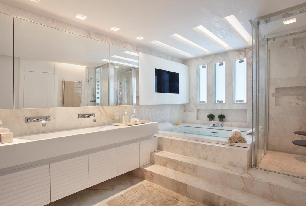 Elegante, este banheiro com dez metros quadrados foi projetado pela arquiteta Leila Dionizios e é revestido totalmente por mármore importado. A área do spa, com TV, fica um pouco acima da linha geral do piso e é dedicada aos momentos de relaxamento. À esquerda, a ampla bancada de Corian tem duas pias esculpidas e acomoda fartos armários