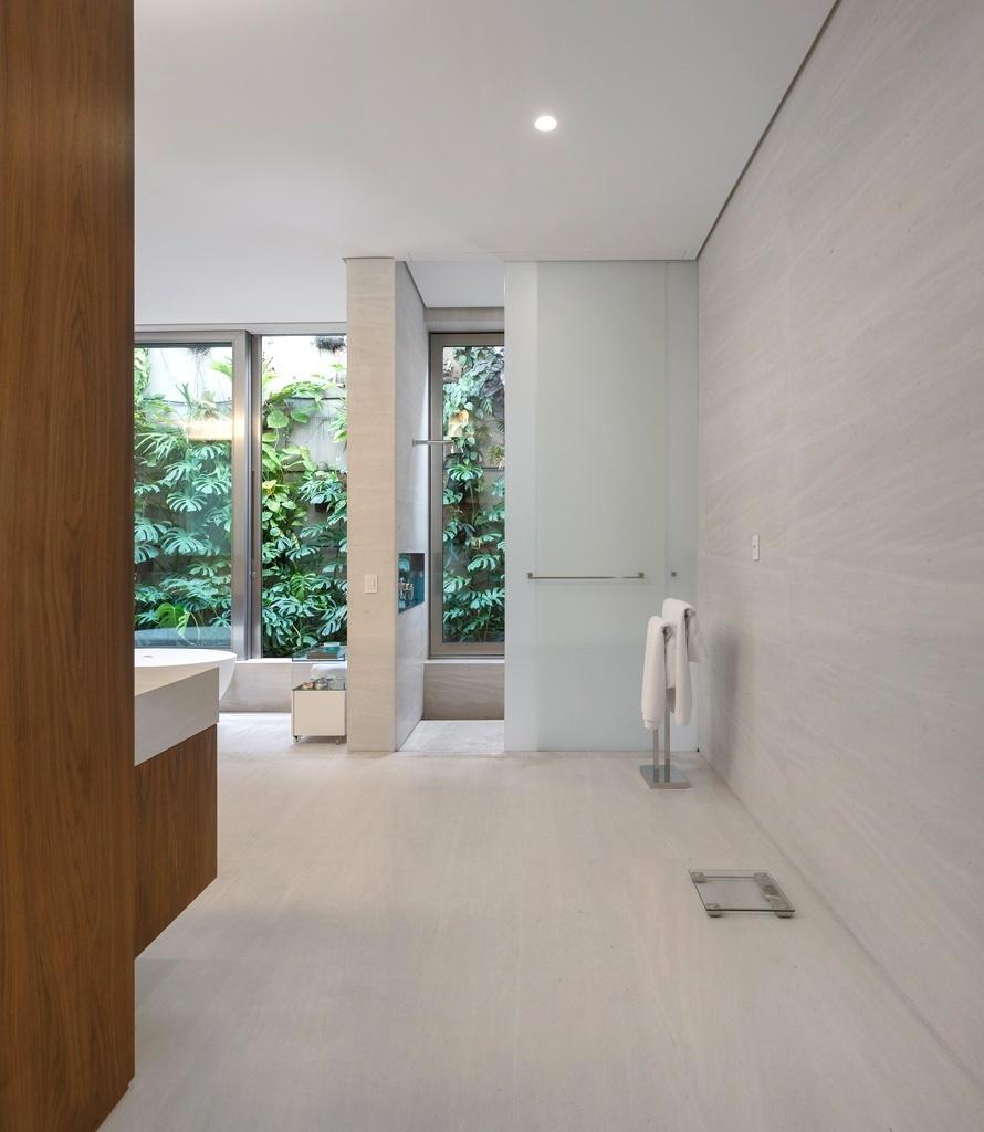 No amplo banheiro idealizado por Fernanda Marques uma porta de correr de vidro fosco dá privacidade à área do boxe, que também se integra ao jardim repleto de costelas-de-Adão