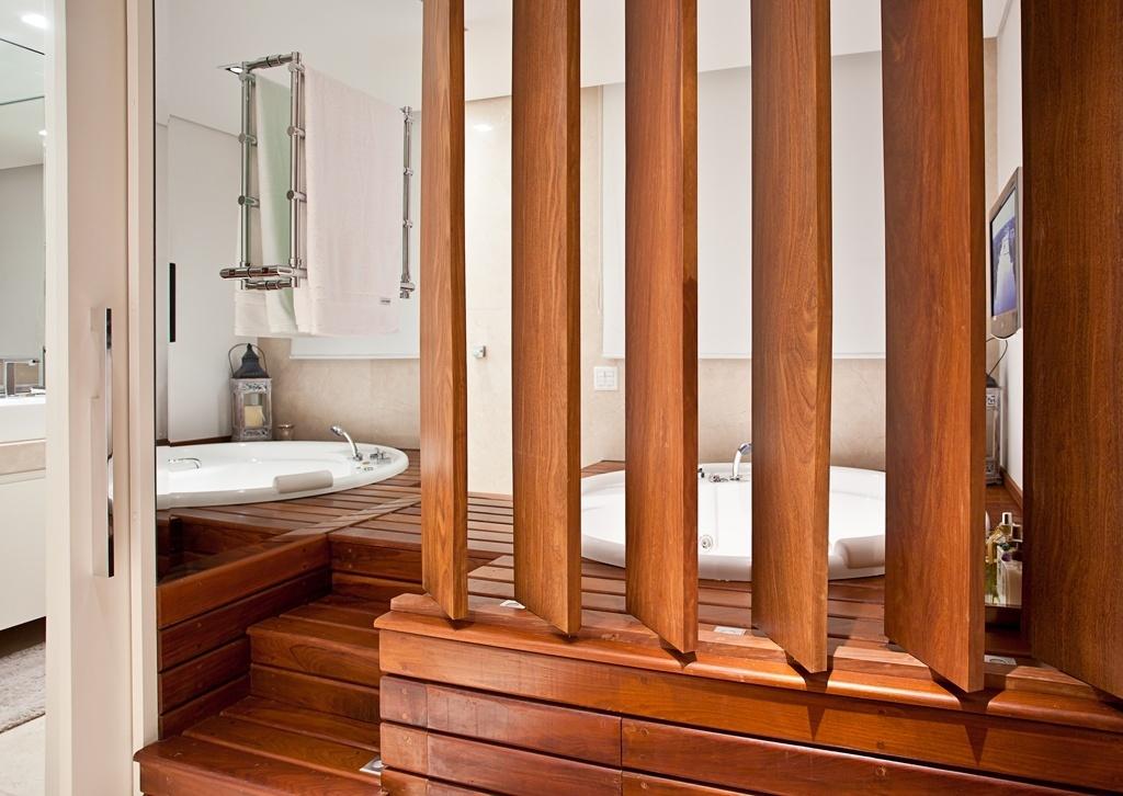 A sala de banho com 16 m² teve spa e banheiro separados pela arquiteta e designer Maithiá Guedes: o primeiro foi instalado em uma plataforma de madeira (itaúba) com acesso tanto pelo quarto que é protegido por brises, quanto pela área molhada