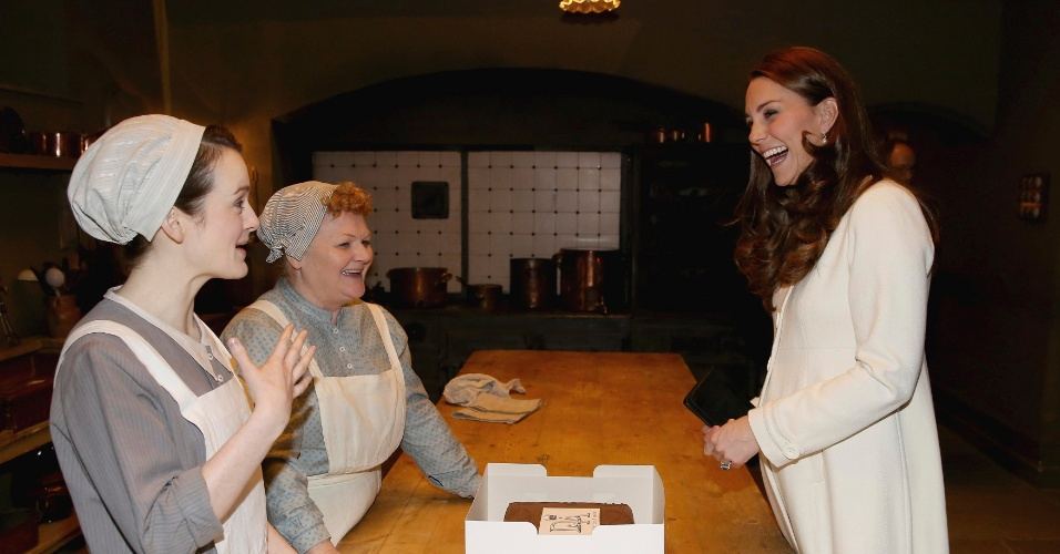 12.mar.2015 - Kate Middleton ganha bolo de chocolate e conversa com as atrizes Sophie McShera e Lesley Nicol durante visita ao set de gravações de