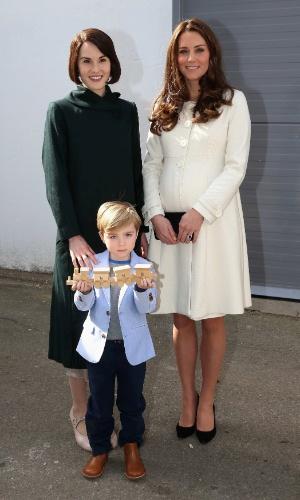 12.mar.2015 - Kate Middleton posa com a atriz Michelle Dockery e o ator-mirim Oliver Barker durante visita ao set de gravações de