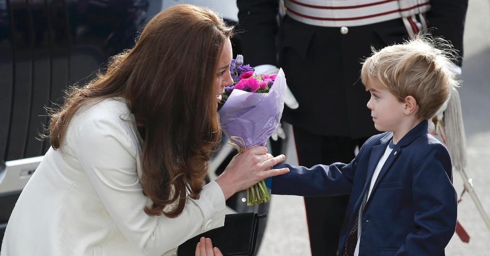 12.mar.2015 - Kate Middleton recebe buquê de flores do ator-mirim Zac Barker ao chegar para visitar os estúdios da série