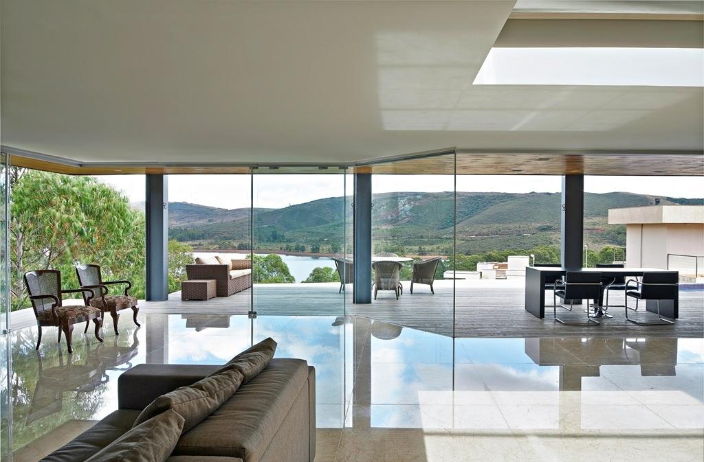 O destaque da sala de estar é o fechamento total em vidros, com máxima integração do interior à paisagem. A entrada massiva de luz natural elimina a necessidade de muitos pontos de luz dire
