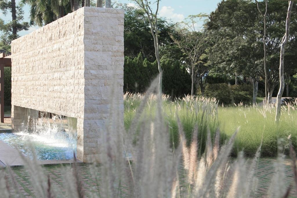 À frente da casa, mudas de capim do Texas emprestam leveza à fonte de pedra criada pela arquiteta Debora Aguiar, responsável pelo projeto e construção da casa. O paisagismo ficou a cargo de Alex Hanazaki e foi premiado, em 2014, como um dos melhores do mundo