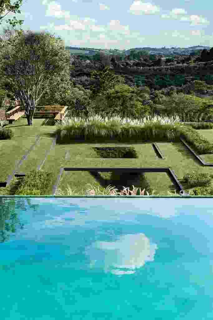 A piscina encontra-se no primeiro nível do terreno, logo abaixo, está o jardim estruturado em platôs criado por Alex Hanazaki e pontuado por poucas espécies como capim do Texas e jabuticabeiras. Essas variedades não interferem na livre apreciação do entorno - Yuri Seródio e Beto Riginik/ Divulgação