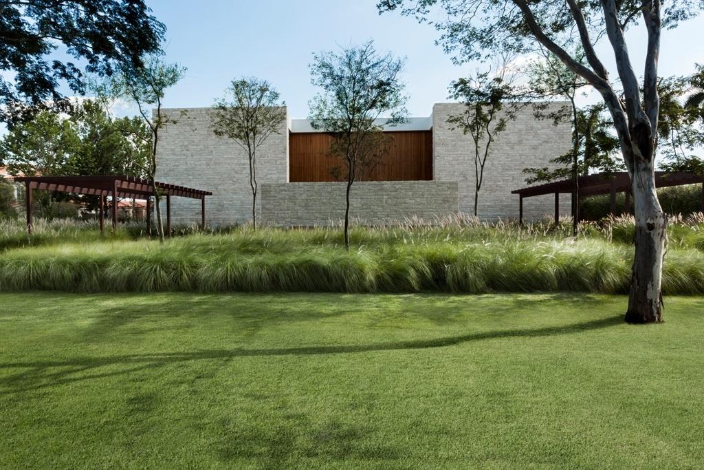 À frente da imponente casa projetada pela arquiteta Débora Aguiar cerca de duas mil mudas de capim do Texas imprimem leveza ao corpo construído. A paisagem, desenhada pelo paisagista Alex Hanazaki, também é pontuada por exemplares de pau ferro