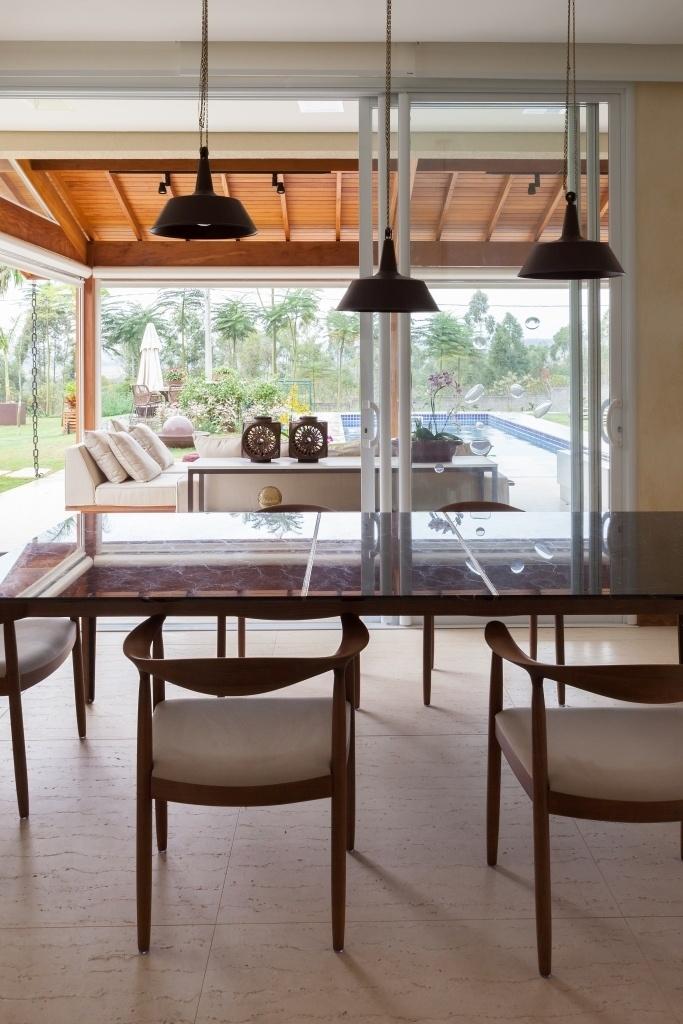 A sala de jantar é totalmente integrada à varanda e à área da piscina, através de portas de correr. O projeto de interiores, do escritório Díptico Design, manteve o piso original da casa, bem como a divisão dos ambientes, tendo especificado apenas os móveis, cuja disposição cria espaços confortáveis de convivência
